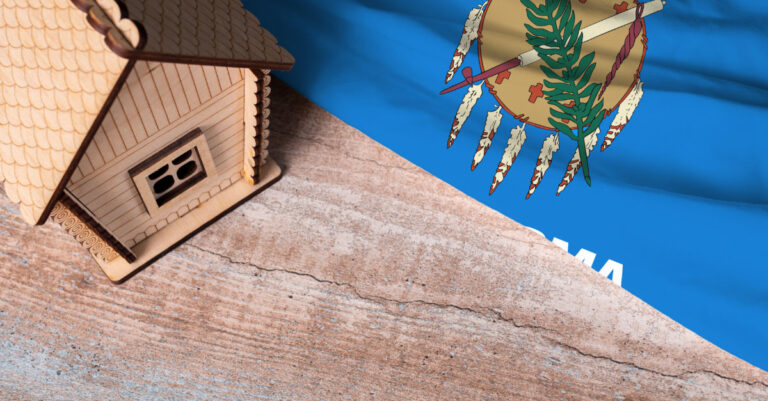 Model house next to Oklahoma flag on wooden surface