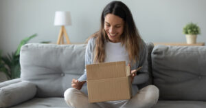 Woman opening package while sitting on couch
