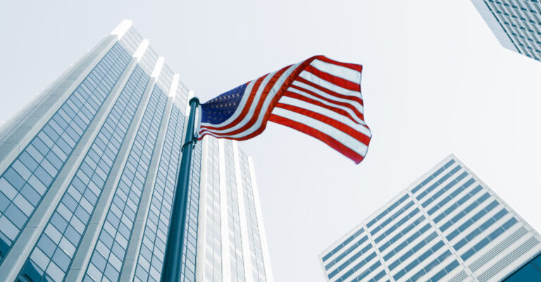 National News - United States Flag seen from ground level surrounded by buildings