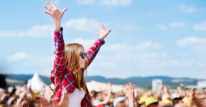 Woman with hands in the air at music festival Fun Activities
